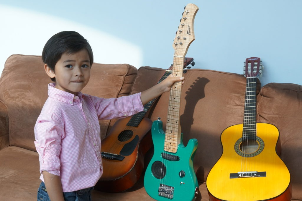 kid picking electric guitar
