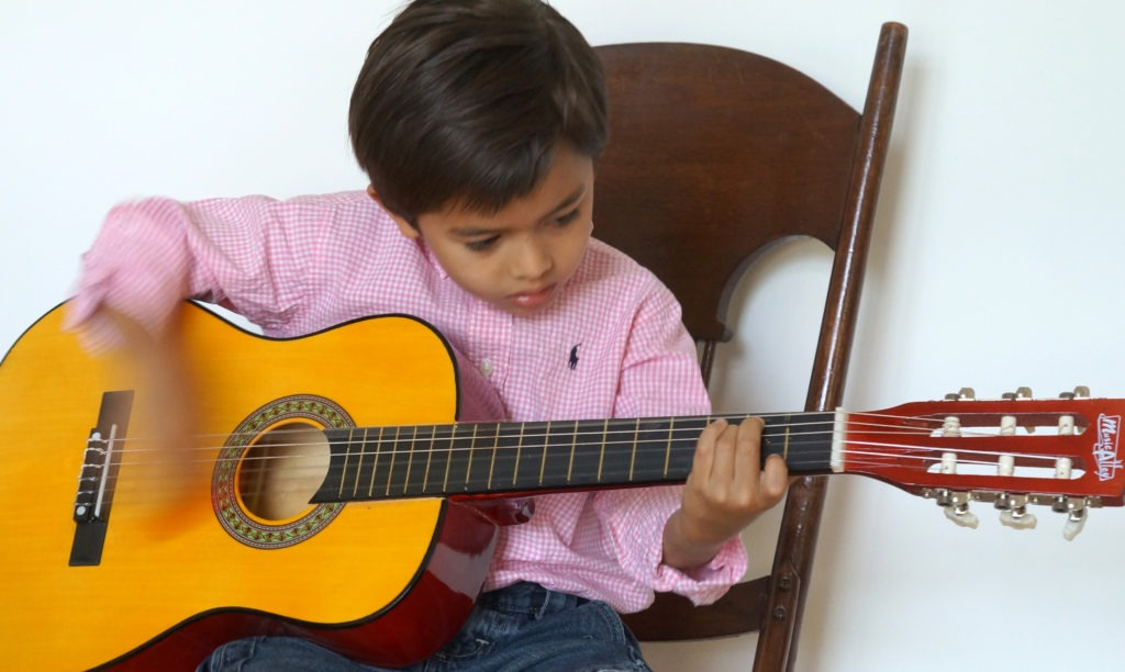 kid-strumming-guitar-lesson